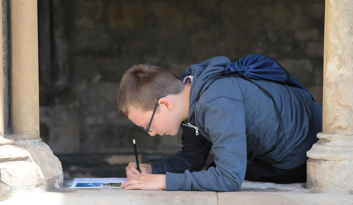 A boy sketches in the cathedral cloisters