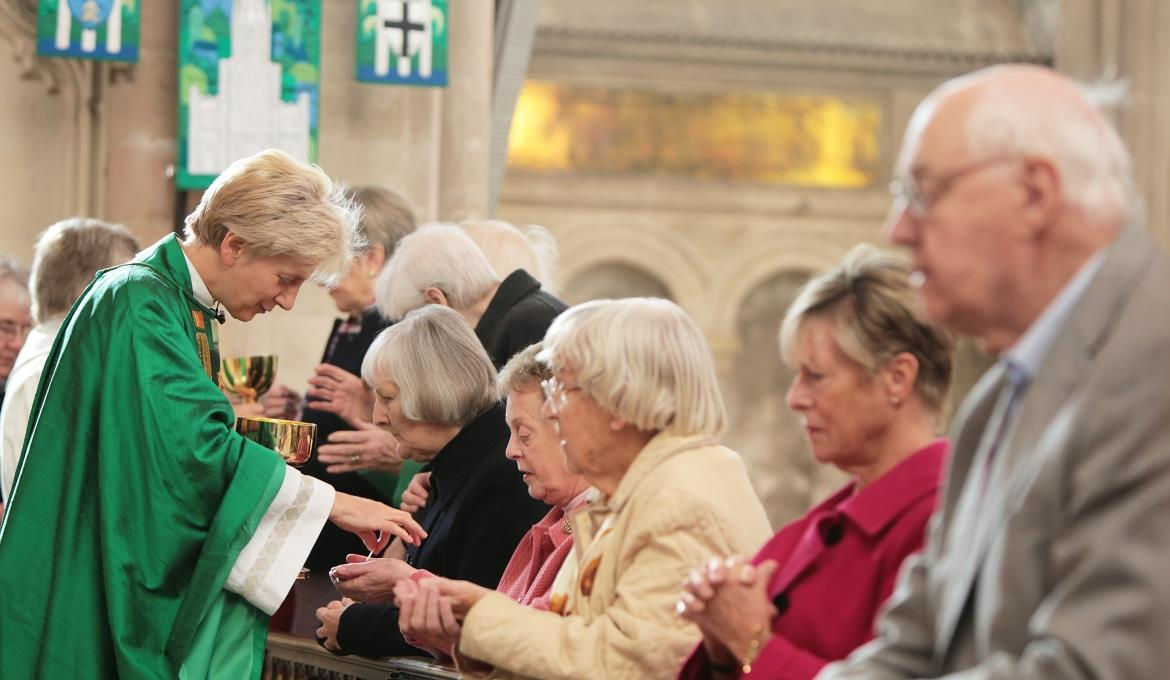 A picture of Dean Jane Hedges giving communion to a member of the congregation