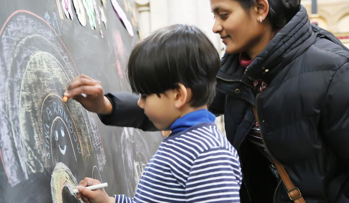 A picture of a mother and son drawing a rainbow on a chalk board