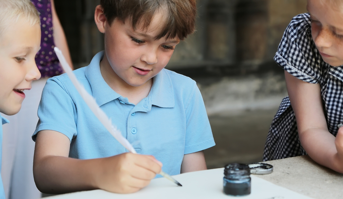 A child tries calligraphy on a school visit