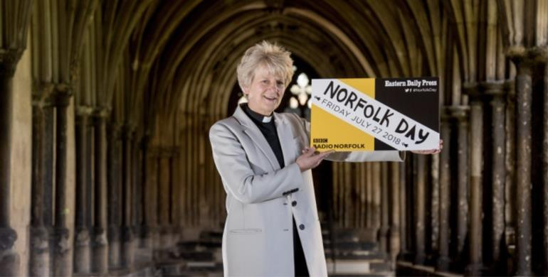 A picture of Dean of Norwich, Jane Hedges, holding a print out of the Norfolk Day logo